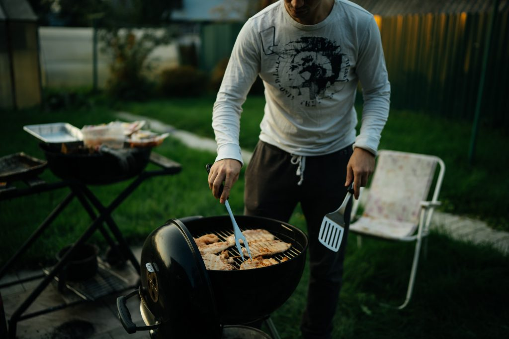person in white long sleeve shirt holding black pan with food