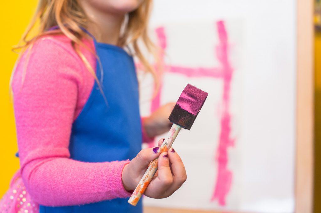 girl using pink paint brush